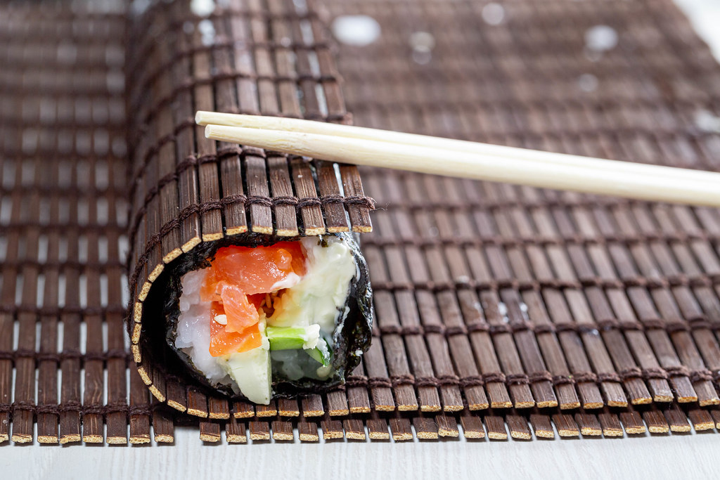 Sushi Roll Wrapped In Bamboo Mat With Chopsticks Marco
