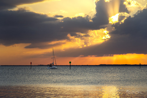 sailboat vessel boat mast rigging sailors navigationlights bay harbor waves chanelmarkers birds orange yellow gold golden clouds beams rays light charlotteharbor poncedeleon historicalpark puntagorda isles pgi sunset intense dramatic beautiful water shore shoreline stevefrazierphotography november 2017 waterscape landscape scene scenery cloudy