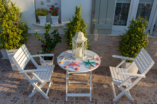 Garden furniture decorated with colorful starfish, on the terrace of a Greek dwelling house in the Cycladic city Naousa