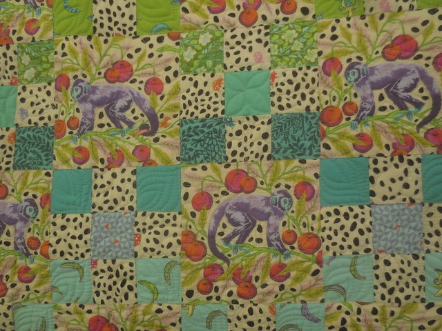 Detail of light and bright quilt featuring monkey print