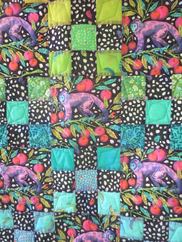 Detail of black and bright quilt featuring monkey print