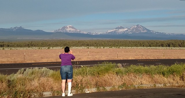 woman taking photo of Three Sisters mountains in the distance