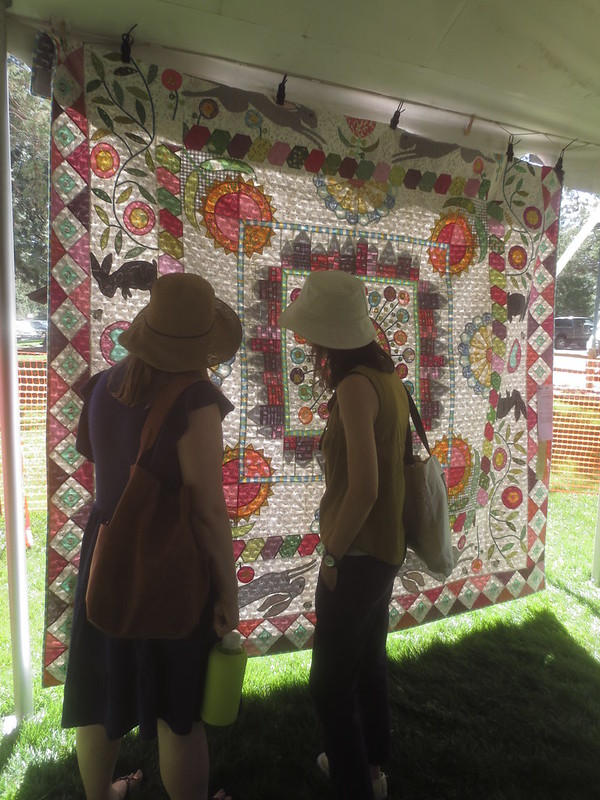 Two women standing in front of a quilt hung in a tent