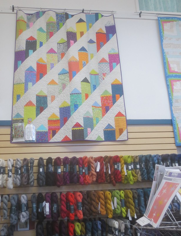 Quilt with houses design on wall of shop