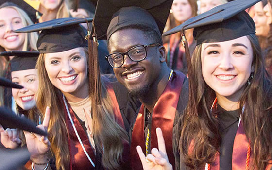 Graduating Students, smiling, giving the Hook 'Em