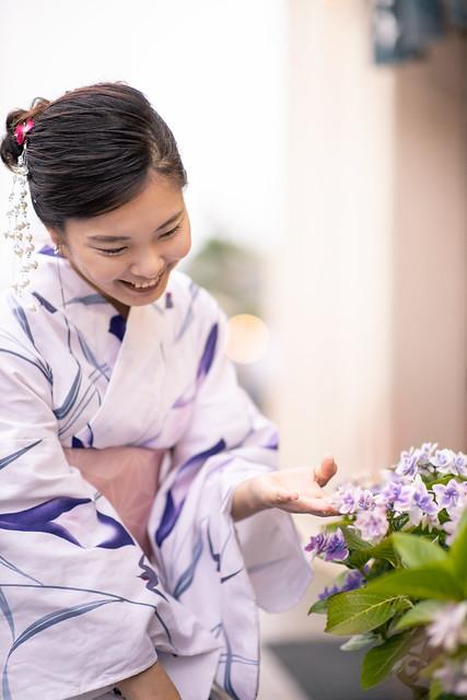 Young woman in yukata touching hydrangea