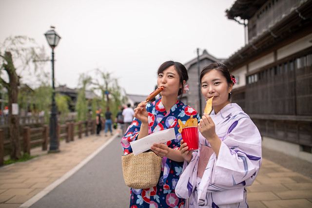 Young women in yukata eating foods on street