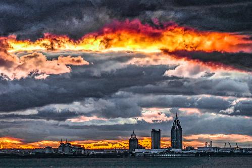 sunset beach mobilebay daphne alabama color sky blue red yellow orange pink clouds storm skyline building