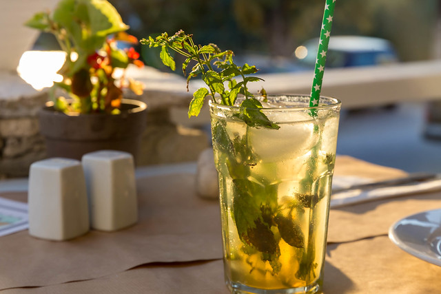 Alcoholic Drink Mojito, with fresh mint leaves, ice cubes and green straw, on an outside table under the sun