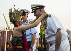 Cmdr. Edward Rosso, commanding officer of USS Montgomery (LCS 8), is greeted by traditional Indonesian dancers as U.S. Coast Guard Capt. Bob Little, commanding officer of USCGC Stratton (WMSL 752), looks on during a welcoming ceremony hosted by the Indonesian Navy, July 31. (U.S. Navy/MC2 Christopher A. Veloicaza)