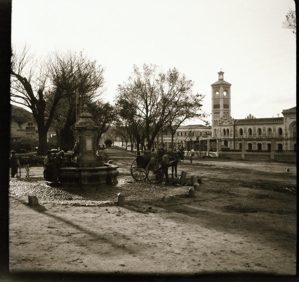 Fuente de Cabrahigos con su olmeda aneja. Al fondo la estación de ferrocarril. Fotografía de Narciso Clavería a comienzos de 1919