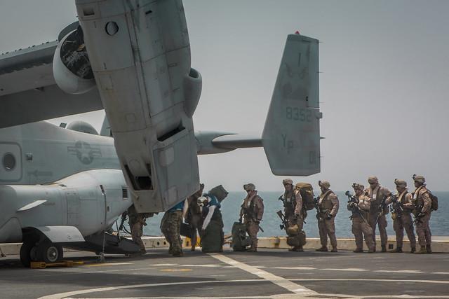 U.S. Marines board MV-22 Osprey aircraft