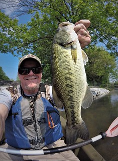 Photo of Man holding a largemouth bass in a kayak