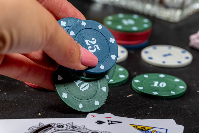 Woman's hand puts on the table chips. The concept of rate increase