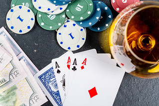 Four aces, chips and money on a black table with a glass of cognac. Top view | by wuestenigel