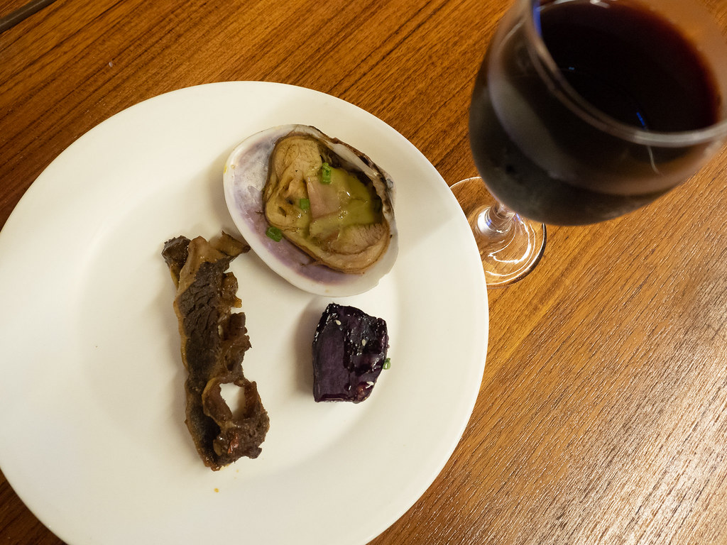 Fine dining at a Jogoya. A slice of grilled beef, Japanese Sweet Potato and grilled clam with a glass of red wine.