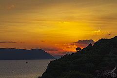 "The sun sets behind a tree on Palaeókastro hill near Loutraki, Skopelos Isl., Greece. An ancient city's citadel was erected there in Ⅴ–Ⅳ century BC. The city's original name remains unknown, but its Roman name was Selin(o)us. The whole island was known as Pepárēthus.  The poem lines may accompany the pictorial mood of the photograph:  ""The broken sunset declined and was gone and it seemed a delusion to ask for the gifts of the sky.""  —George Seferis (Erotikos Logos, transl. by Edm. Keeley)"