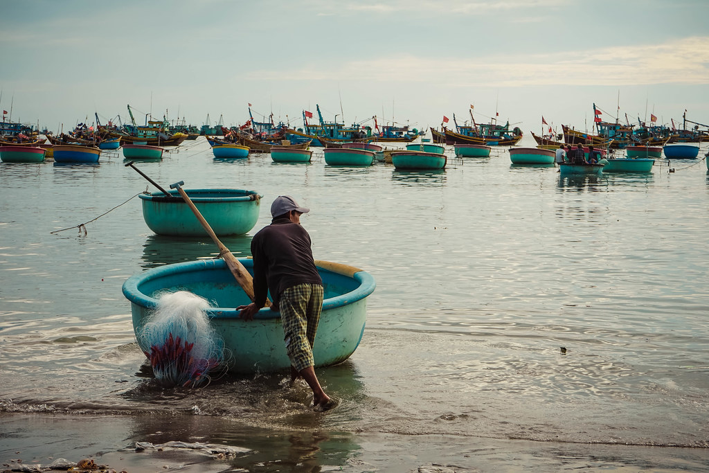 A fishermen pushing his blue basket boat into the sea