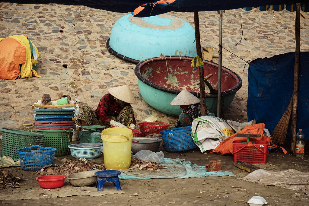 Two women sorting out fish from colorful baskets