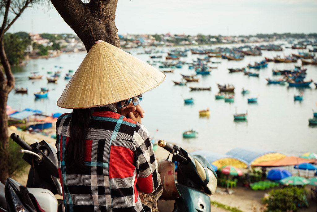 A woman wearing a Vietnamese hat is looking towards the sea, where hundreds of blue boats and baskets are anchored