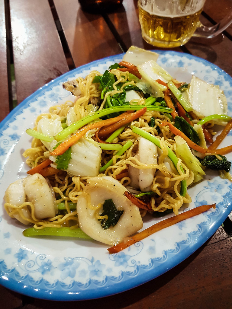 A colorful plate of seafood noodles, with carrots, cabbage and a lot of fish