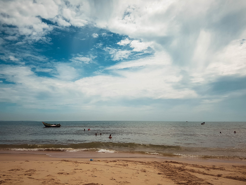 A part of the public beach in Mui Ne, with people swimming in the sea and a small boat passing by