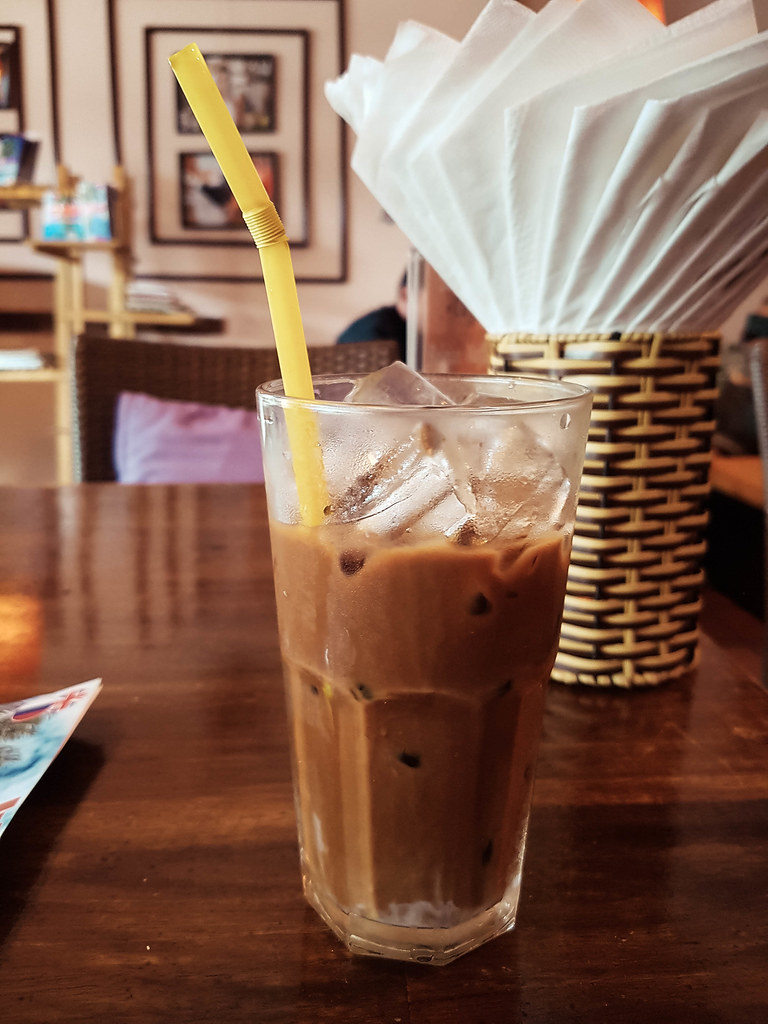 A glass filled with cold coffee and ice put on a brown table.