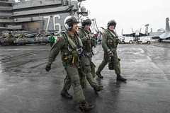 Capt. Forrest Young, left, and Capt. Michael Rovenolt, far right, walk away from their aircraft on the flight deck of USS Ronald Reagan (CVN 76) after Carrier Air Wing 5's change of command ceremony, Aug. 2. (U.S. Navy/MC2 Tyra M. Campbell)