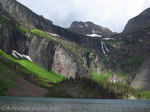 The sun shines momentarily over Grinnell Lake in Glacier National Park, Montana