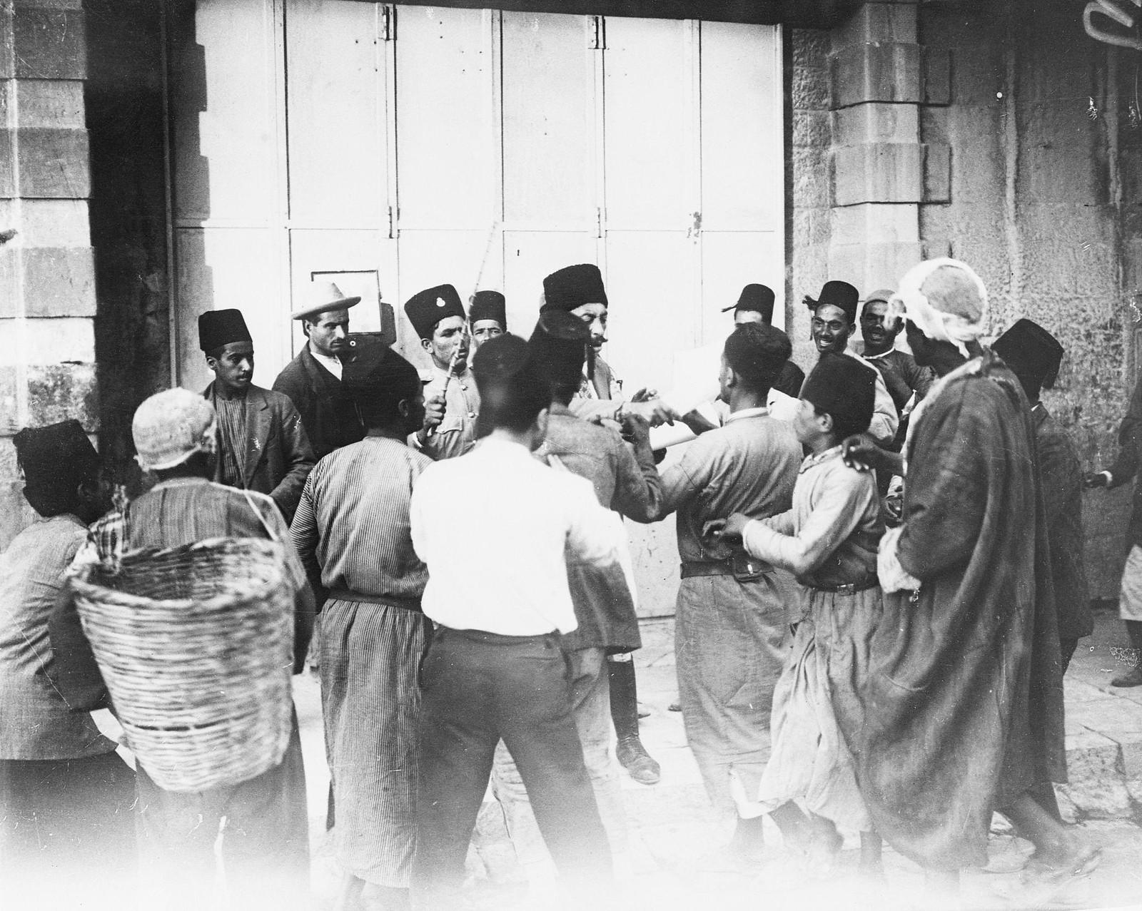 . 23–31 августа. Иерусалим. Группа палестинцев слушает прокламацию, выпущенную британским верховным комиссаром, в которой говорится, что любые нарушения правопорядка будут рассматриваться британским военным судом