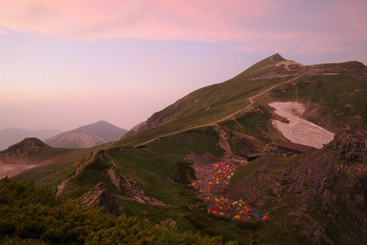 夕日に染まる白馬岳とキャンプ場