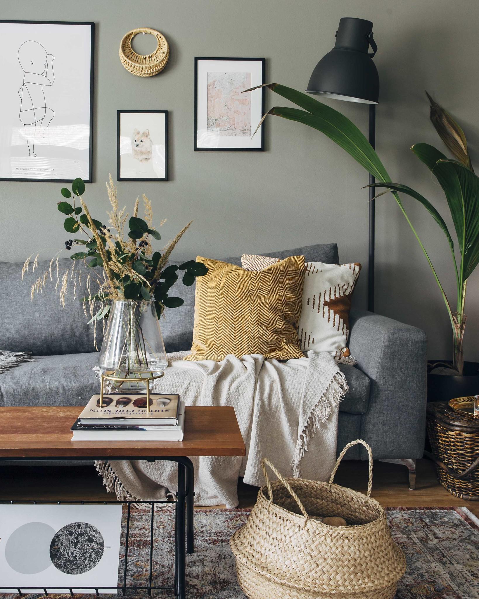 Boheemi olohuone, jonka kahvipöydällä on kimppu oksista ja heinästä.
