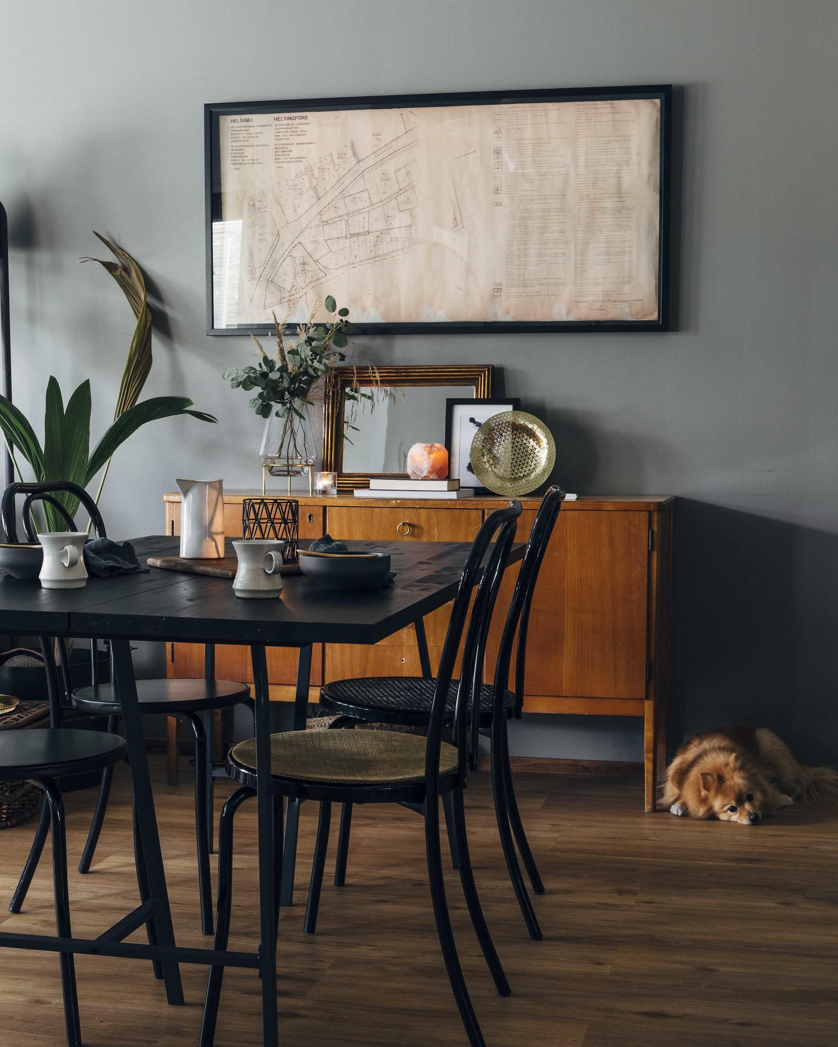 Musta ruokapöytä, jonka takana on vintage senkki.