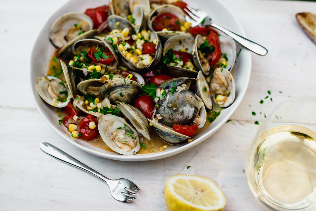 Steamed Clams with Corn and Tomatoes is the perfect summer dinner. Finish with fresh lemon juice and lots of crusty bread for dipping into the broth.