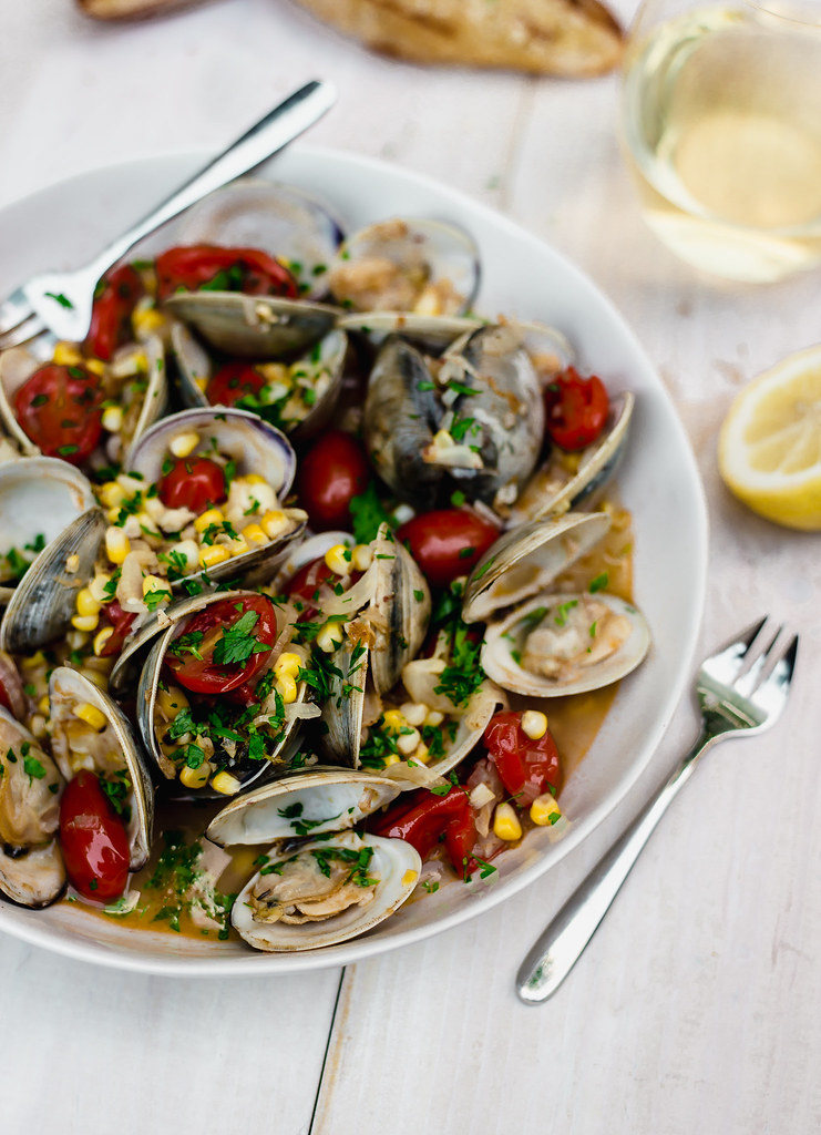 Steamed clams with corn and tomatoes is the perfect summer dinner. Finish with fresh lemon juice and herbs and lots of crusty bread for dipping into the delicious broth