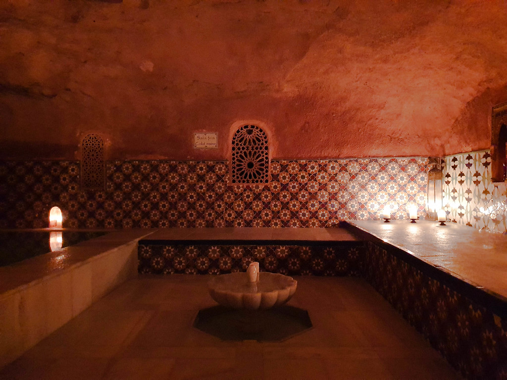 a relaxation room from Hammam Al Andalus. There is a white marble fountain in the middle of the room. The walls are covered with mosaic in flowery Arabic patterns. There is an arabic window on the wall as well.