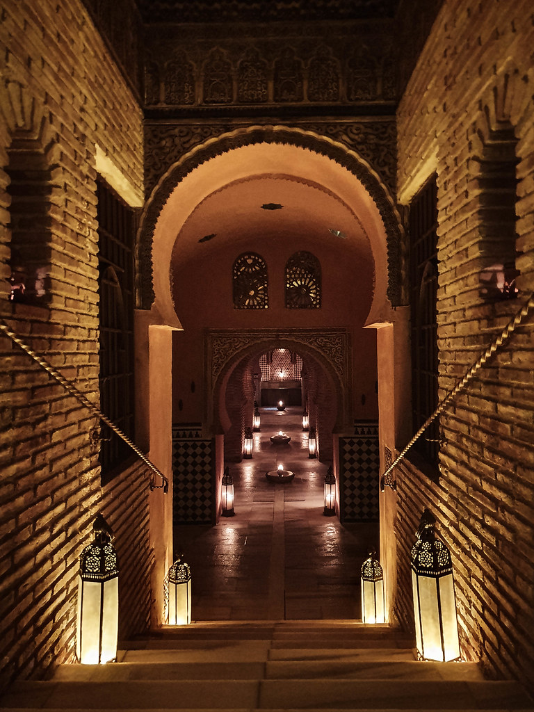 the entrance to the treatment room at Hammam AL Andalus: brick walls, tall candles on the floor, Arabic keyhole arches following the stairs going down