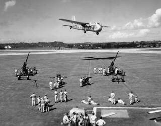 1952 RNZAF Bristol Freighter NZ5902 flying over two 3.7 inch anti aircraft guns on the ground as part of an open day flying display at RNZAF Whenuapai