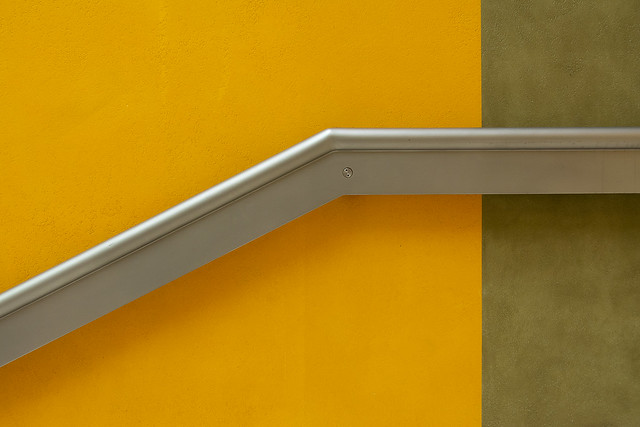 Handrail on a yellow and green wall