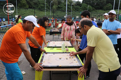 Devotee playing Carom board