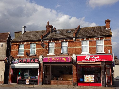 The end of a terrace of two-storey (a different terrace from both the two previously pictured, and with rather more modest architecture). There are shopfronts on the ground floor and rectangular windows above.