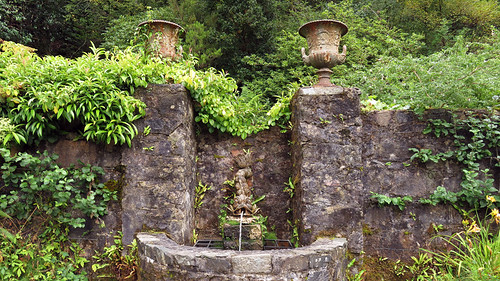 A stone wall with a dolphin fountain in the castle garden in Glenveagh National Park in Ireland