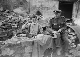 A Japanese-Canadian volunteer shaving outside his dugout, Arras, France / Volontaire canadien d'origine japonaise se rasant à l'extérieur de son abri enterré, Arras (France)