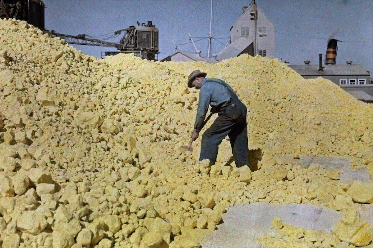 1928. Галвестон, Техас – мужчина лопатой укладывают серу на складе у причала. Клифтон Р. Адамс