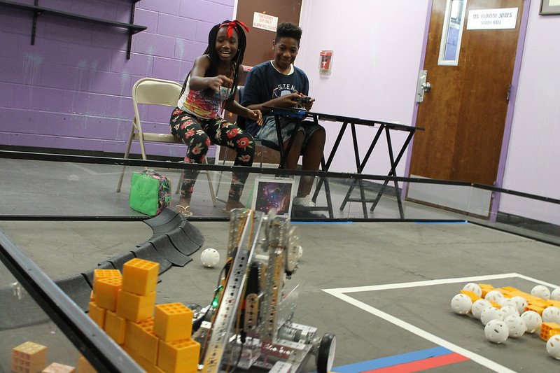 Girl and boy operating robot