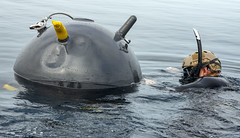 Lt. Andrew Kuo, assigned to EODMU 5 attaches a dummy explosive charge to floating mine during Mine Warfare Exercise (MIWEX) 2JA. (U.S. Navy/MC2 Mario Coto)