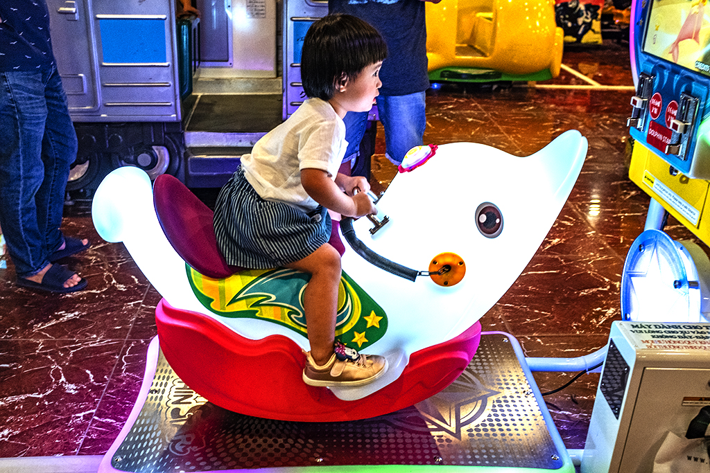 Girl on arcade dolphin at Aeon Mall--Saigon
