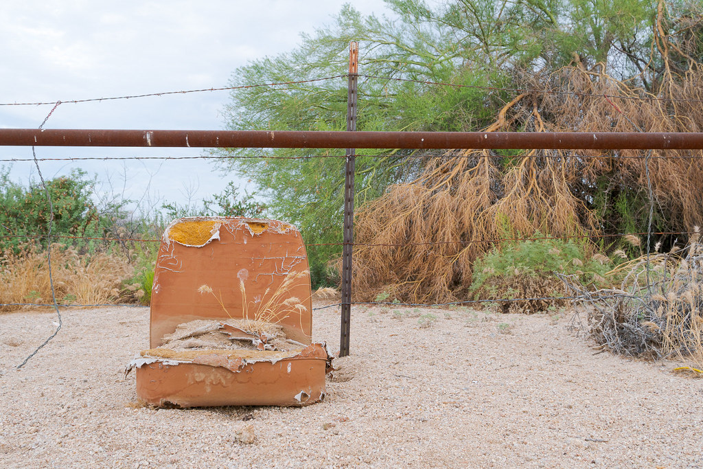 A frontal view of a dilapidated chair sitting in the middle of a desert wash beside the Gooseneck Trail in McDowell Sonoran Preserve in Scottsdale, Arizona in July 2019
