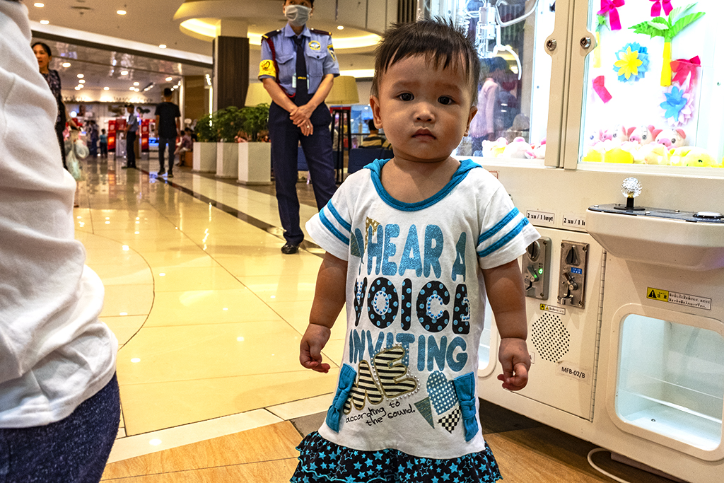 Small girl wearing an I HEAR A VOICE INVITING ME dress at Aeon Mall--Saigon
