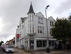 A three-storey end-of-terrace building (not the same terrace as depicted above) with a pointy tower at the corner and a decorative roofline on the main-road frontage.  The entrance is below the tower, and the ground floor has plate-glass display windows.